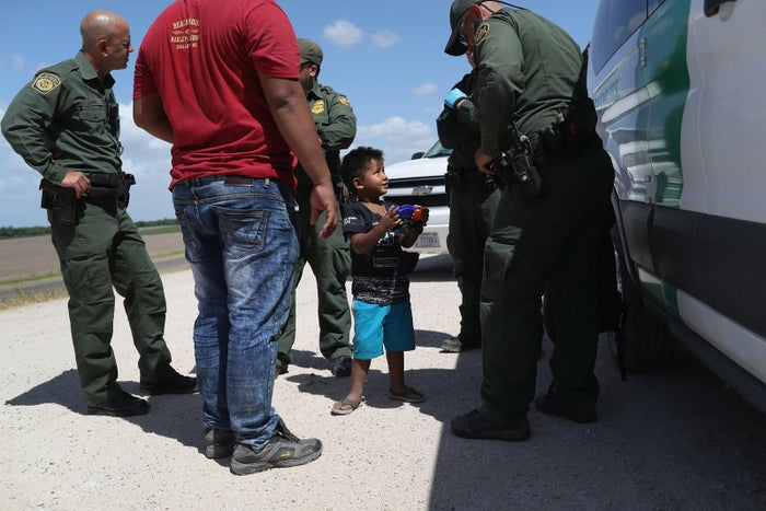 A boy and father from Honduras are taken into custody by US Border Patrol agents on June 12 near Mission, Texas.
