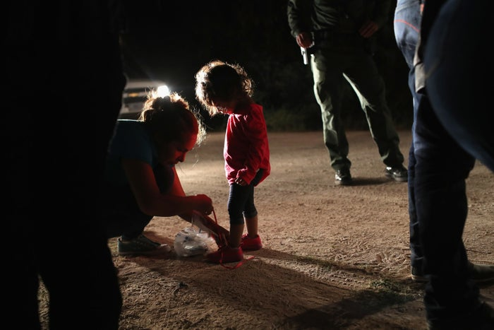 A Honduran mother removes her 2-year-old daughter's shoelaces, as required by US Border Patrol agents, on June 12 in McAllen, Texas.