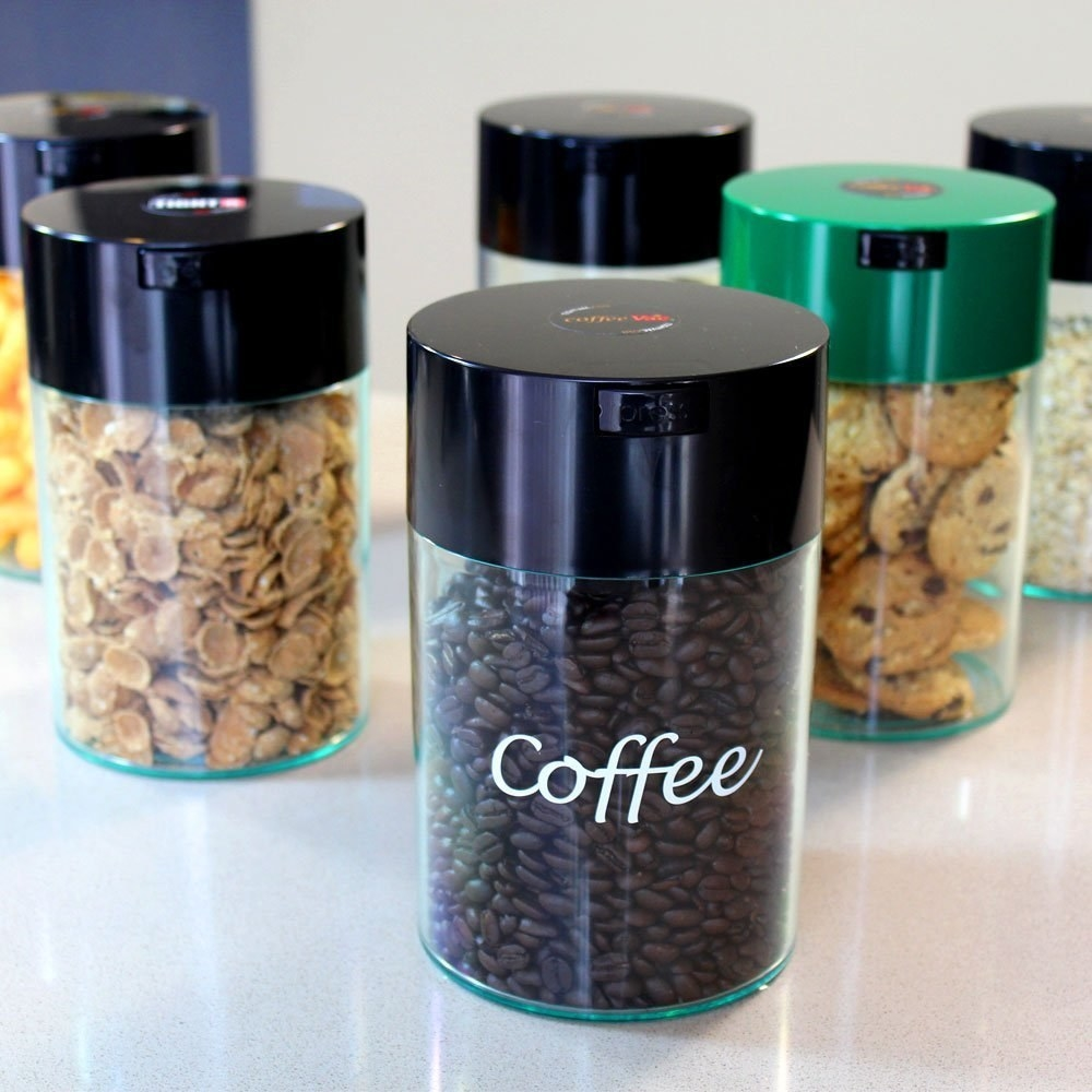 "A clear container filled with coffee beans, topped with a black lid; the word ""Coffee"" is printed on the front in white letters"