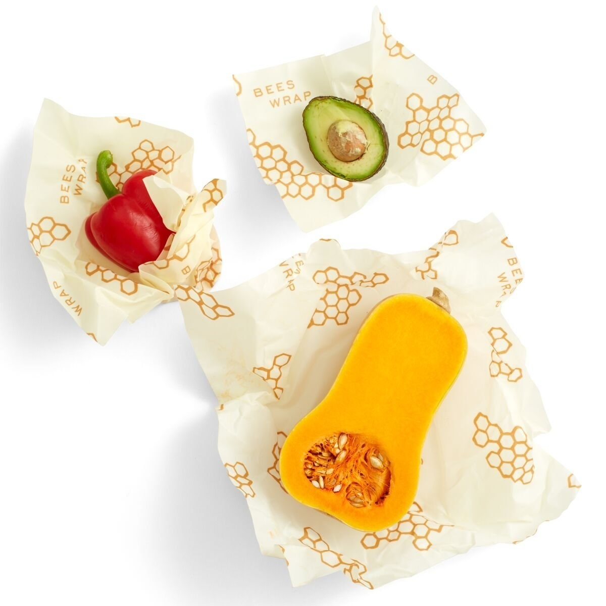 The beeswax wrap opened to reveal half of each of a butternut squash, a red bell pepper, and an avocado