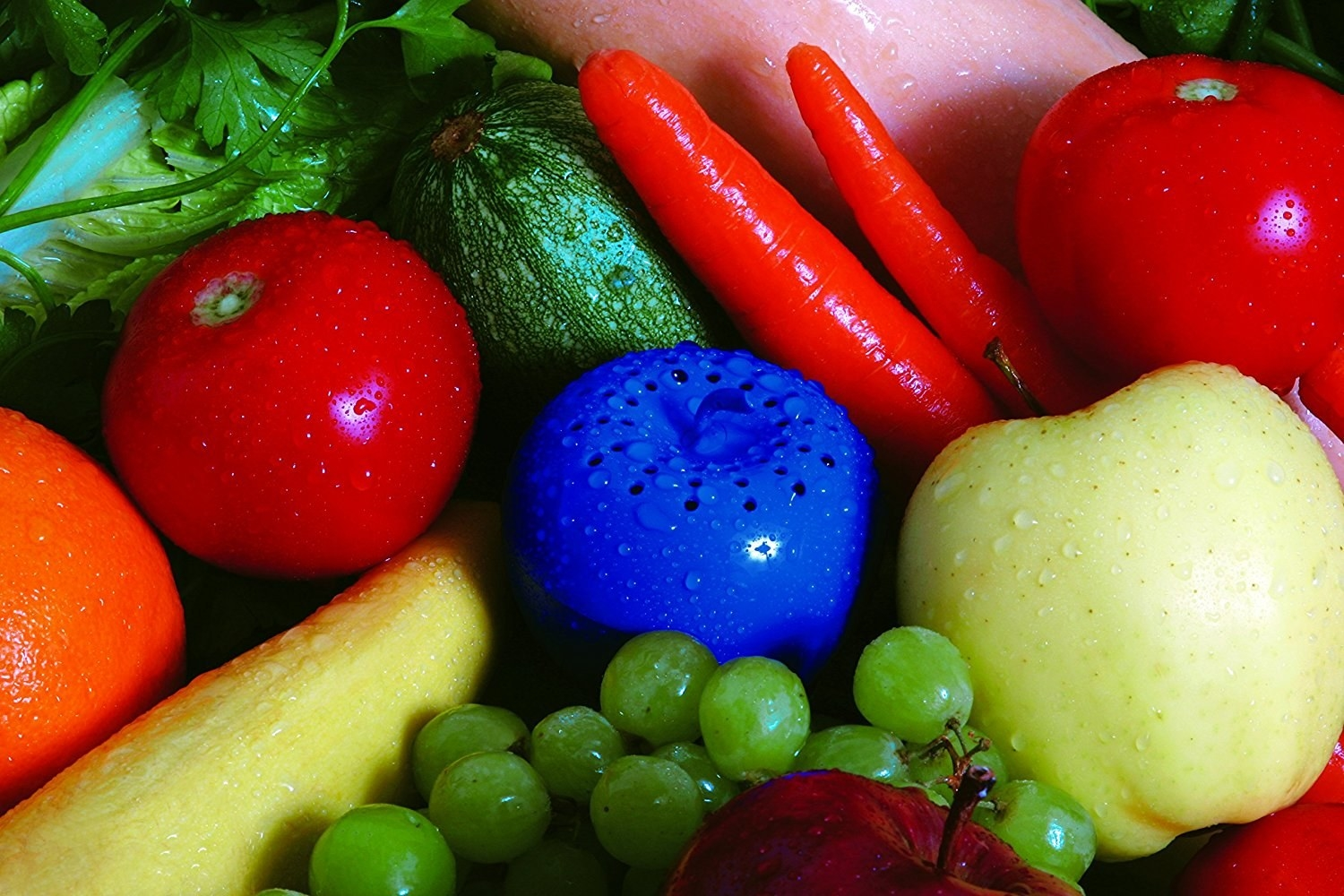 The blue plastic apple, with holes on top, nestled next to a bunch of fruit and veggies