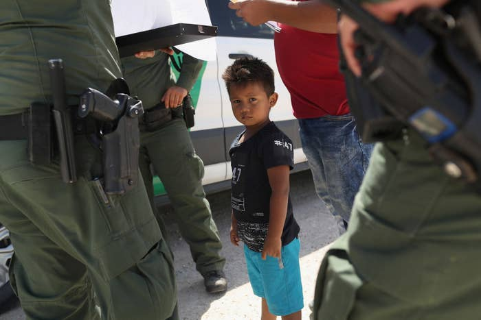 US Border Patrol agents take a father and son from Honduras into custody near the US–Mexico border June 12 near Mission, Texas.