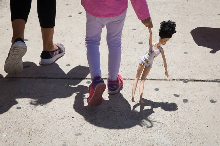 A 4-year-old Honduran girl carries a doll while walking with her mother, both immigrants released from detention to a nearby bus station on June 17 in McAllen, Texas.