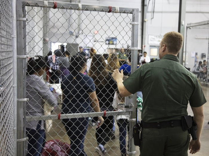 A border patrol agent watches as people who've been taken into custody related to cases of illegal entry into the United States stand in line at a facility in McAllen.