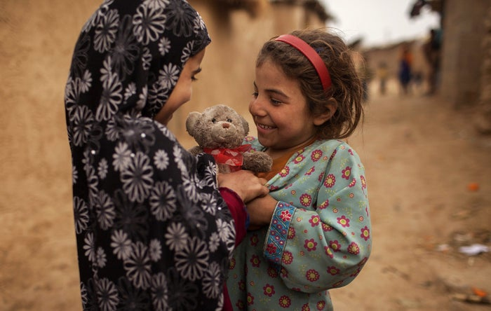 An Afghan refugee girl gives a stuffed toy to her friend on Valentine's Day in the outskirts of Islamabad, Pakistan, on Feb. 14, 2014.