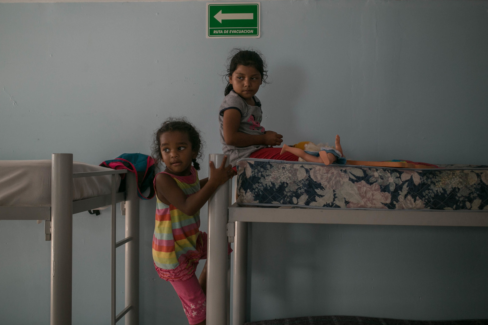 Claudia's daughter, 6, and Piedad's daughter, 3, play with toys on a bunk in the shelter where the family is staying.