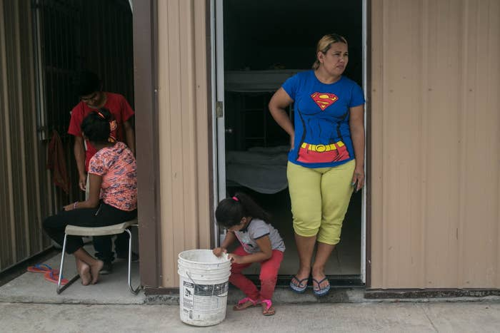 Claudia, with her 6-year-old daughter, looks out from her shared room at a shelter in Reynosa.