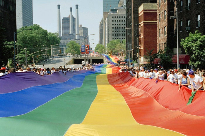 A mile-long rainbow is carried past the United Nations secretariat building in New York City on June 26, 1994.
