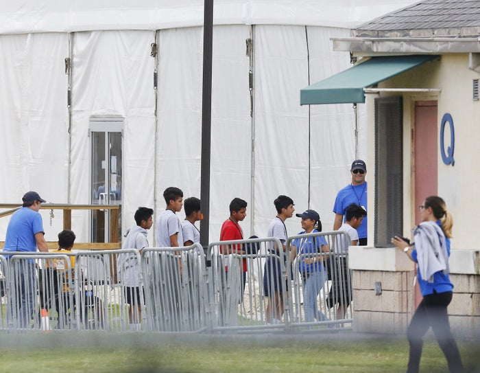 Immigrant children walk in a line outside a temporary shelter in Homestead, Fla.