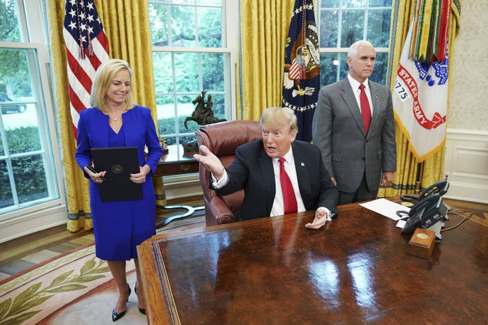 Watched by Homeland Security Secretary Kirstjen Nielsen and Vice President Mike Pence, President Donald Trump signs an executive order on immigration in the Oval Office of the White House on June 20, 2018.