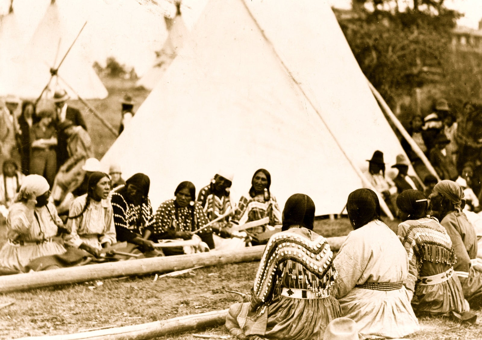 Native American women play a stick game at a midsummer celebration.