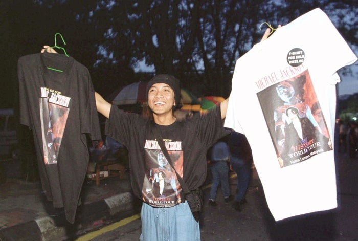 A young hawker sells Michael Jackson T-shirts outside the Kuala Lumpur stadium where Michael Jackson performed in 1996.