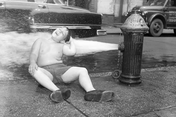 A boy enjoys the water from a gushing fire hydrant in New York City's Lower East Side, 1957.
