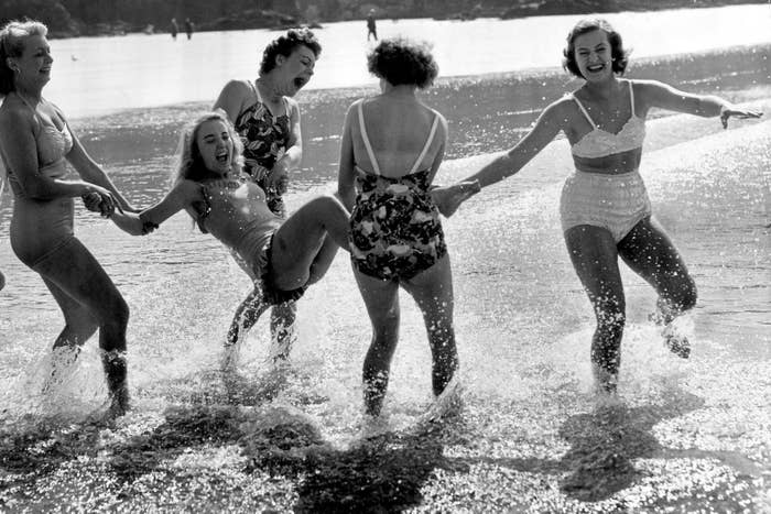 A group of friends plays in the sea at Newquay, Cornwall, 1952.