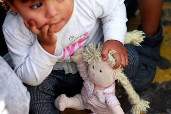 A member of a family from Mexico fleeing violence holds her doll while waiting to enter the United States to meet US Customs and Border Protection officers in Ciudad Juárez, Mexico, on June 20.