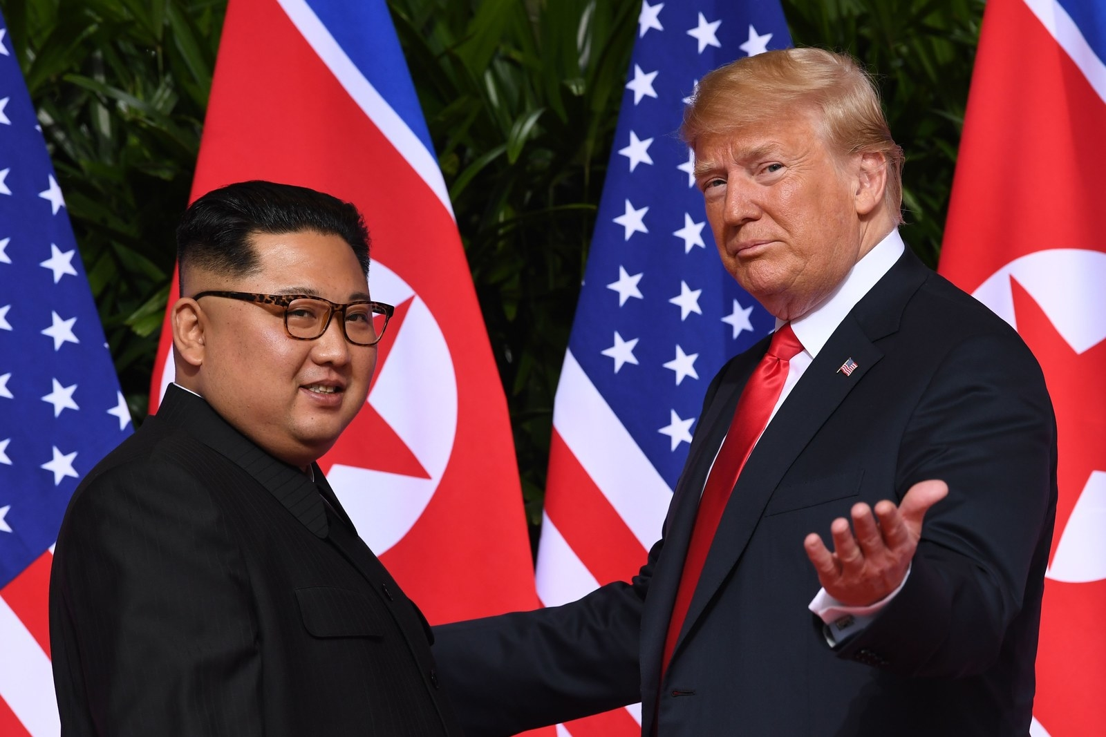Kim Jong Un and Donald Trump shake hands at the start of their summit.