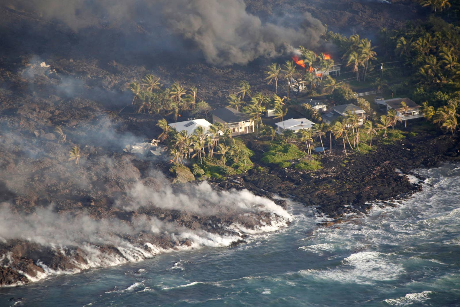 Homes burn from lava that also flowed into the ocean near Kapoho.