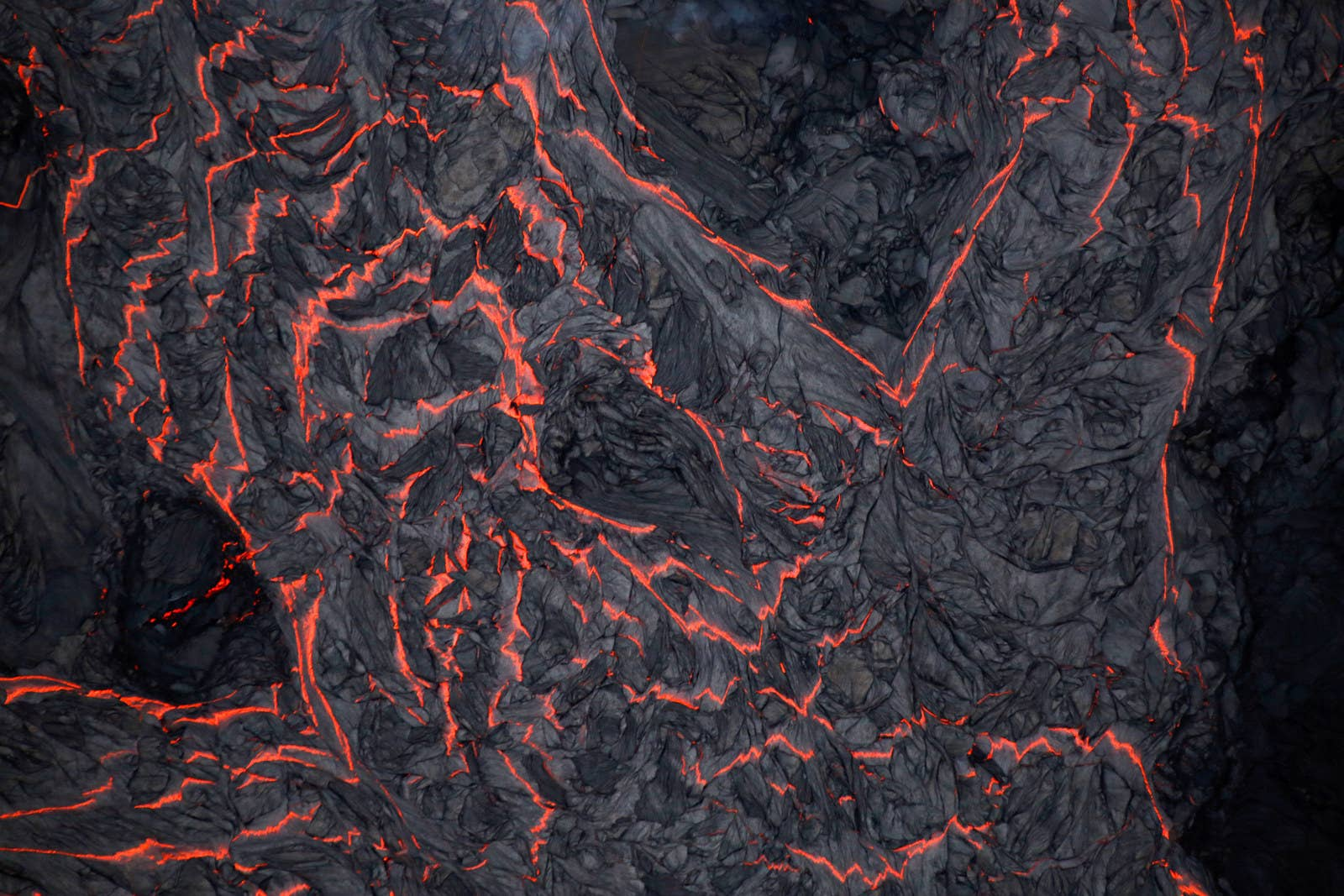 An aerial view of a river of lava, with some of it hardening on top.