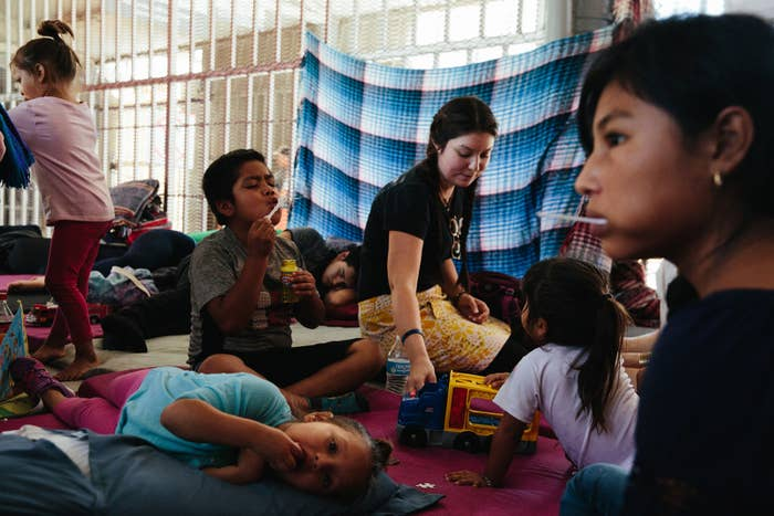 Volunteer Danah Taylor of Tucson (center) plays with children waiting at the border crossing between Nogales, Sonora, and Nogales, Arizona.