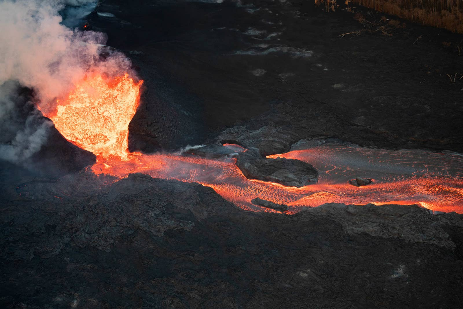 Lava erupts from a fissure, surrounded by a horseshoe-shaped wall of hardened lava.
