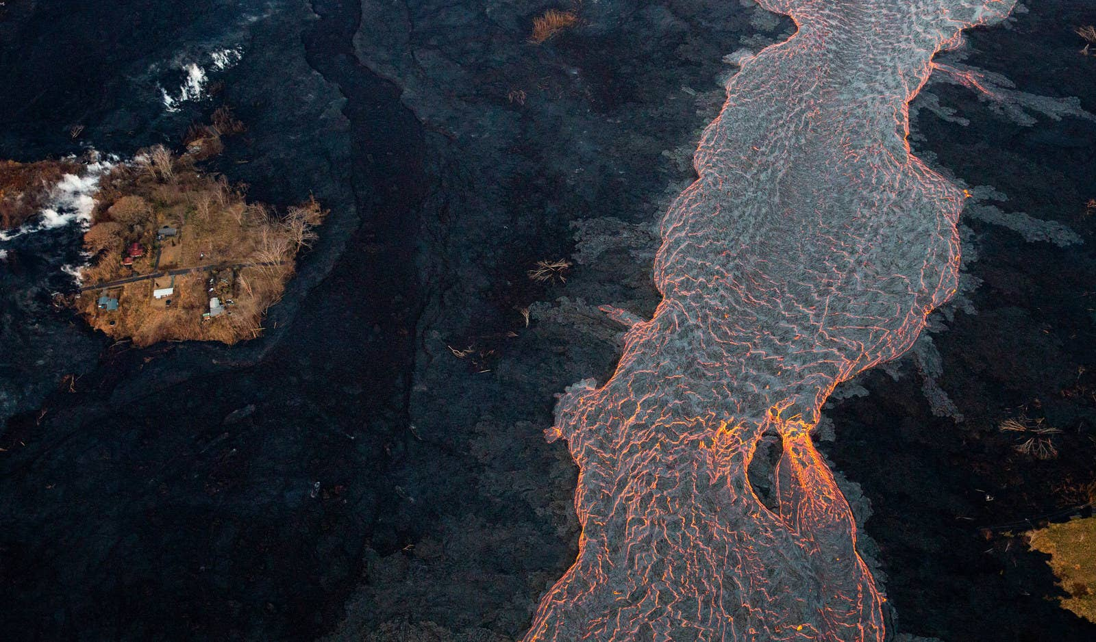 "A channel of lava flows near a ""kipuka,"" or island of untouched homes."