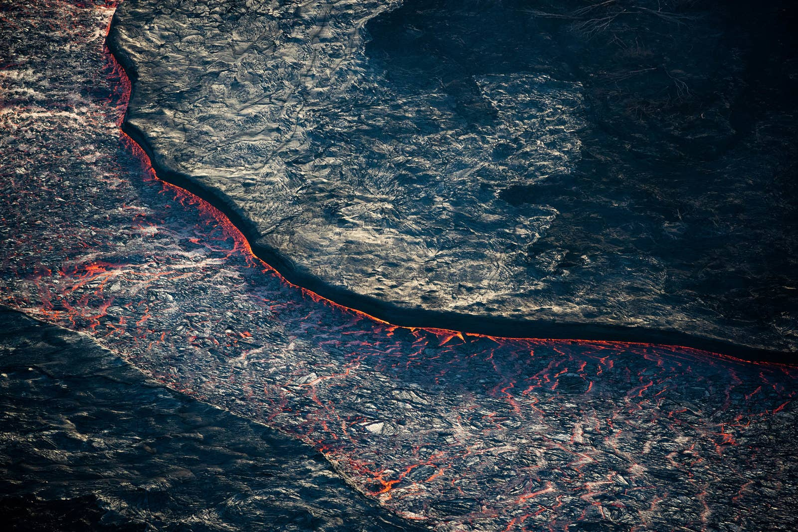 A river of red-hot lava is seen flowing through a channel of hardened lava. At its peak, the lava has moved as fast as 22 mph.