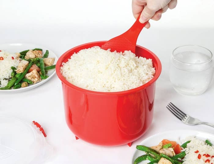 Hand scooping rice out of the cooker with a paddle