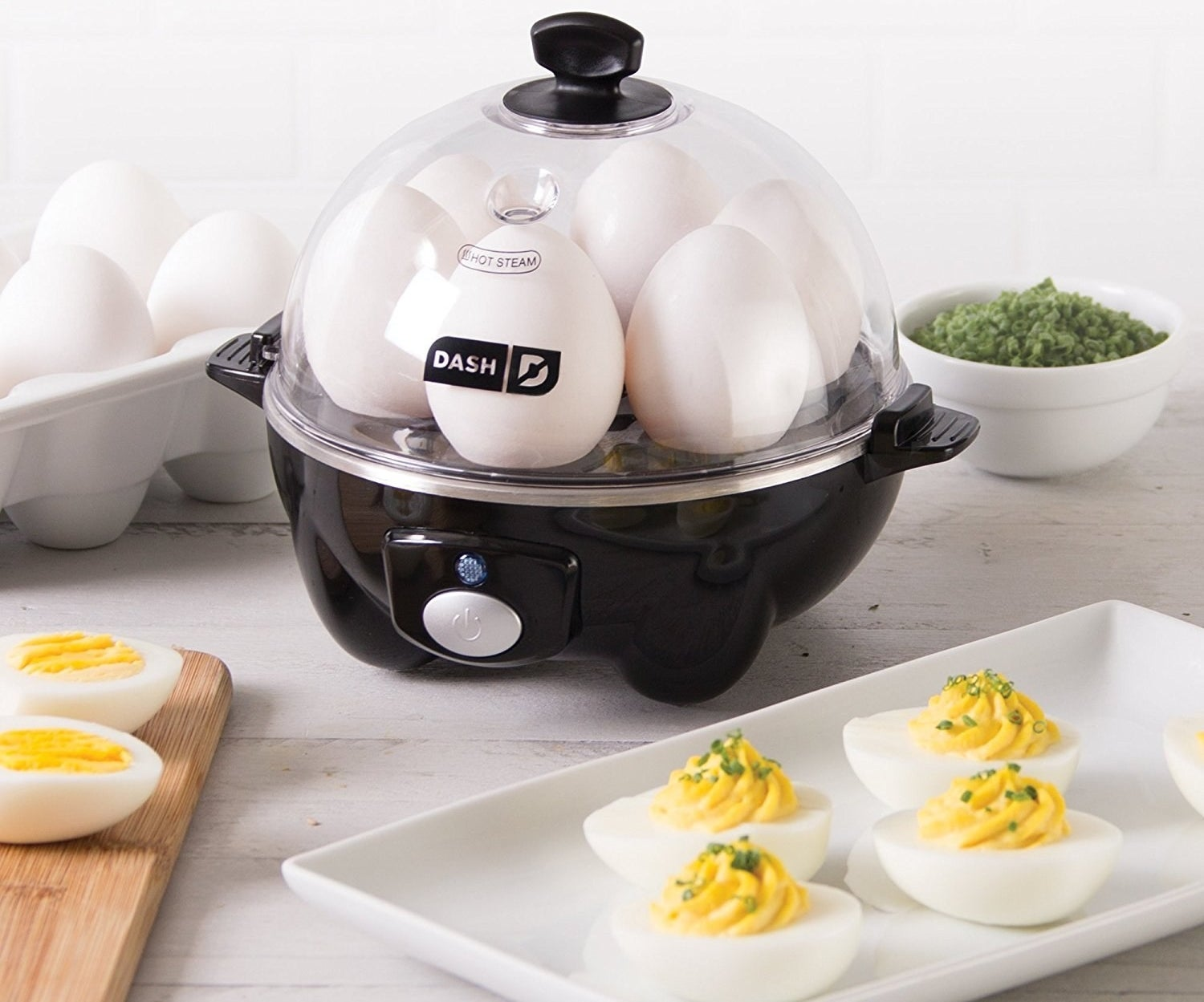 The egg cooker with six eggs in it, plus a plate of deviled eggs