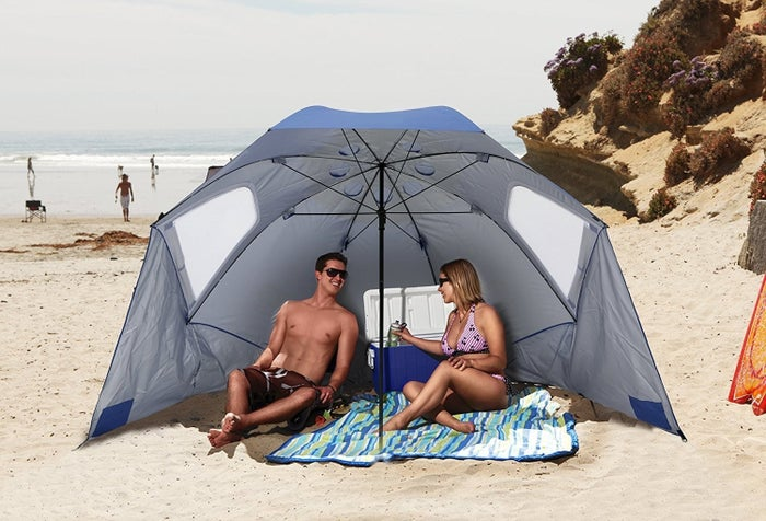 "Promising review: ""Best. Beach. Purchase. EVER. We bought this tent umbrella for the beach after our daughter was born. There was plenty of room underneath for my 6'5"" husband to sit in his large camping chair, our five-month-old daughter to lounge in her travel bassinet, and me to sit in the shade on my towel. 10/10 definitely recommend. The wind vents unzip easily to let the draft blow through so it isn't lifted up. The sand pockets definitely help, too, and it comes with plenty of stakes so you can secure it in the sand. It provides plenty of shade. We took it to a barbecue for the Fourth of July, and it was a hit with all the moms and their babies. We spread out three towels to let the babes play and hang out in the shade. It's definitely large enough to accommodate two chairs underneath for easy beach lounging. I love it."" —Laura MuldoonGet it from Amazon for $48.99 (available in two colors)."