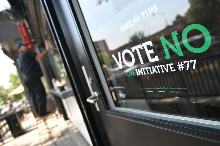 "A man stands near a ""Vote No on Initiative #77"" sign in Washington, DC. Voters approved the measure to raise the minimum wage for tipped restaurant workers."