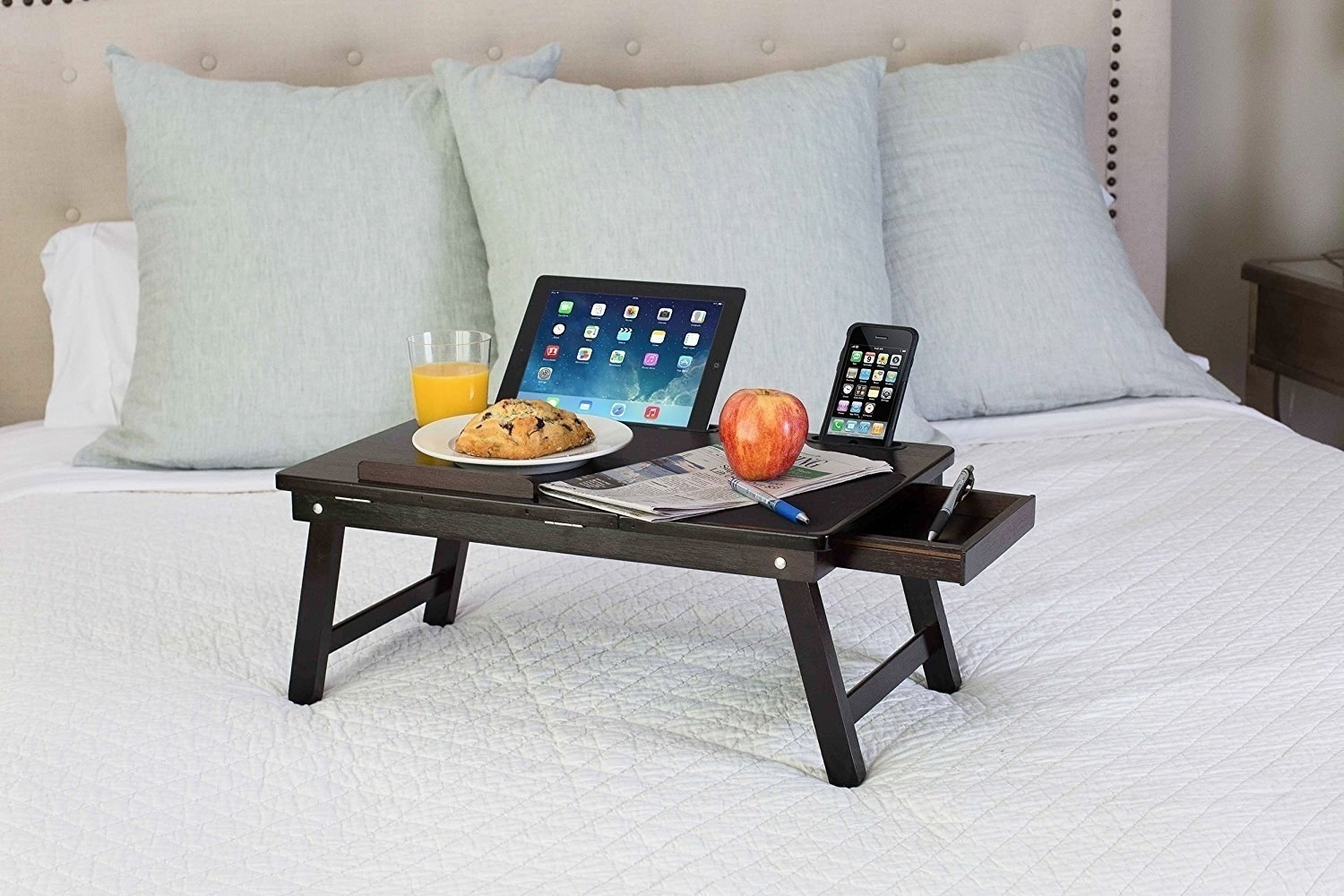 The bed tray holding a tablet, juice, phone, notepad, and more