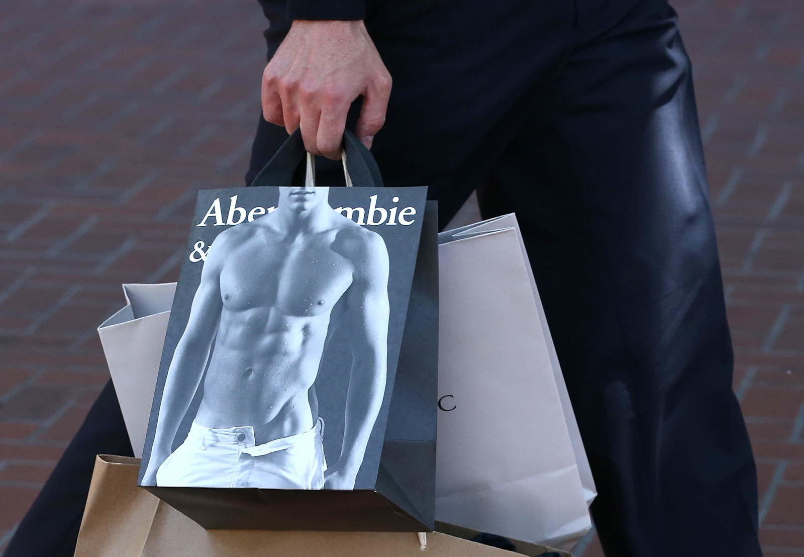 Person holding bags and one is an Abercombie bag with shirtless guy on it