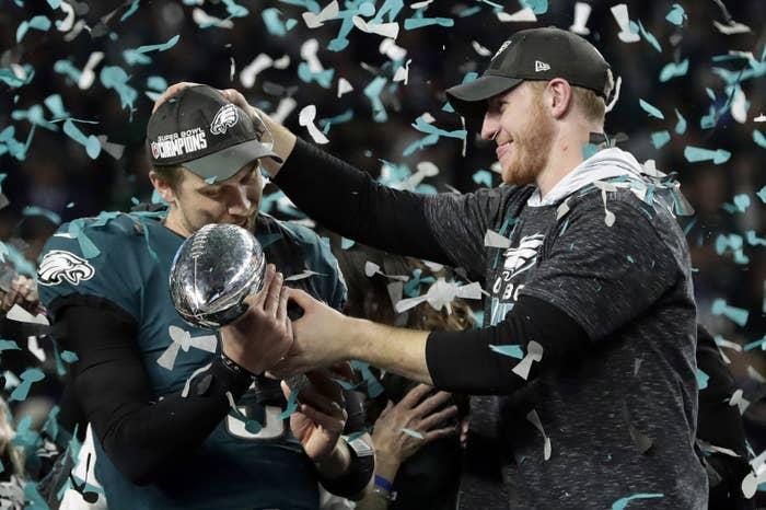 Philadelphia Eagles quarterback Carson Wentz (right) hands the Vincent Lombardi Trophy to Nick Foles after winning NFL Super Bowl 52.