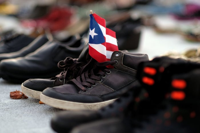 View of a Puerto Rican flag placed on a pair of shoes among hundreds displayed in memory of those killed by Hurricane Maria.