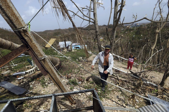 Jose Trinidad walks near the debris of his destroyed home in Montebello, Puerto Rico, in the aftermath of Hurricane Maria, Sept. 26, 2017.
