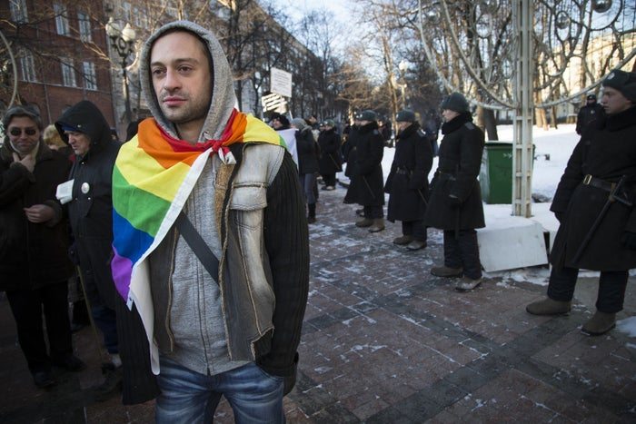 A Russian gay rights activist walks along a police line during a rally in Moscow ahead of the 2014 Sochi Winter Olympics.