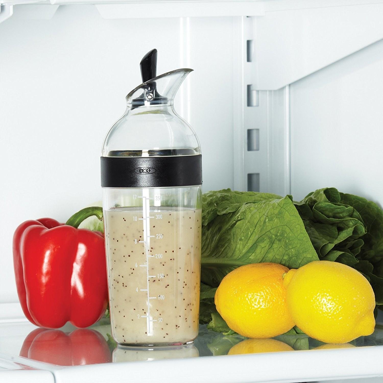 The shaker, filled with vinaigrette in a fridge