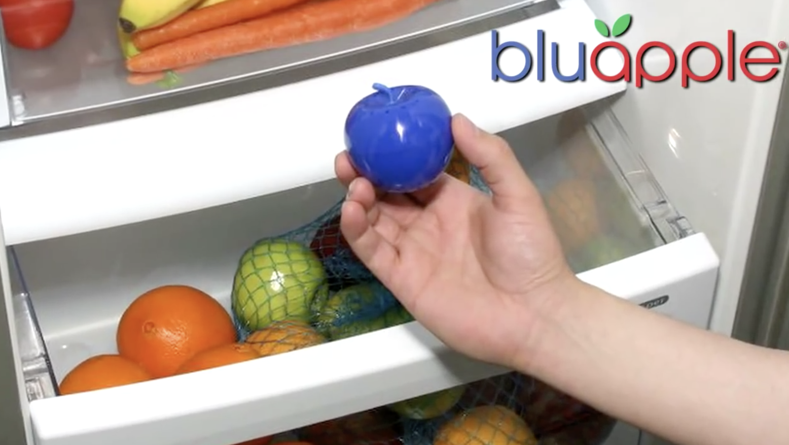 A hand holding the blue apple-shaped product above a fridge drawer full of produce