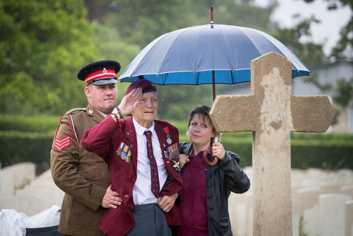 Ray Shuck, 95, who was a paratrooper on D-Day and was later shot in the head by a German sniper, salutes a memorial cross that commemorates his fallen comrades in the cemetery in Ranville, France, on June 5. He is helped up by Sgt. Kirk Blakemore and D-Day Revisited volunteer Kate Rousseau.
