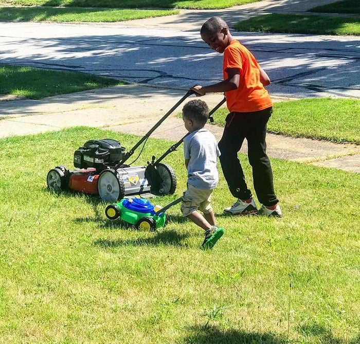 Reggie mows the lawn while showing a younger kid how it's done.