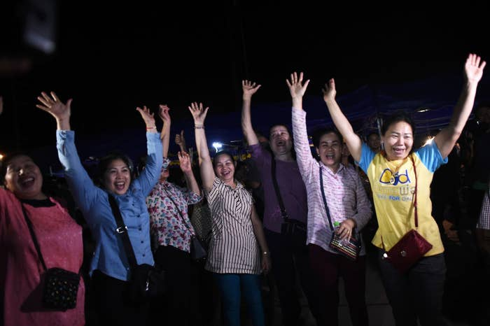 Volunteers celebrate at a makeshift press centre in Mae Sai district of Chiang Rai province on Tuesday.