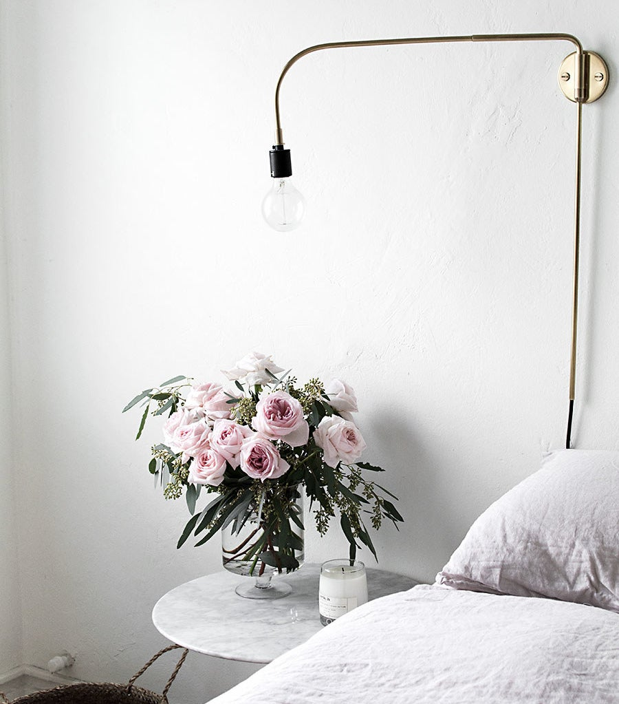 A gorgeous bouquet of pink roses sitting on a bedside table.