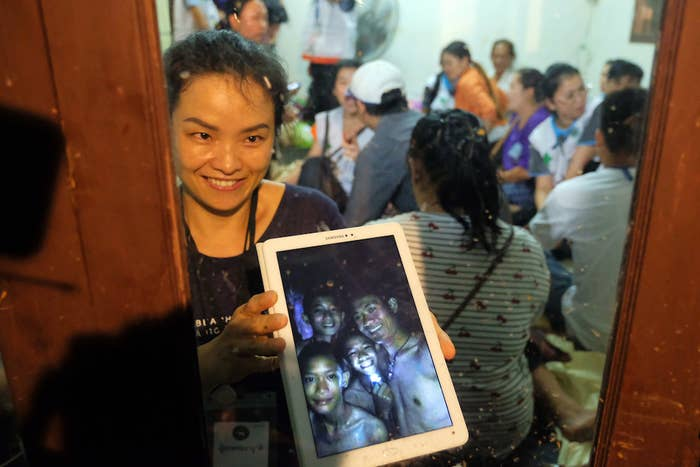 Relatives of the missing boys show photos of them after the 12 boys and their soccer coach have been found alive in the cave where they've been missing for over a week after monsoon rains blocked the main entrance on July 2.