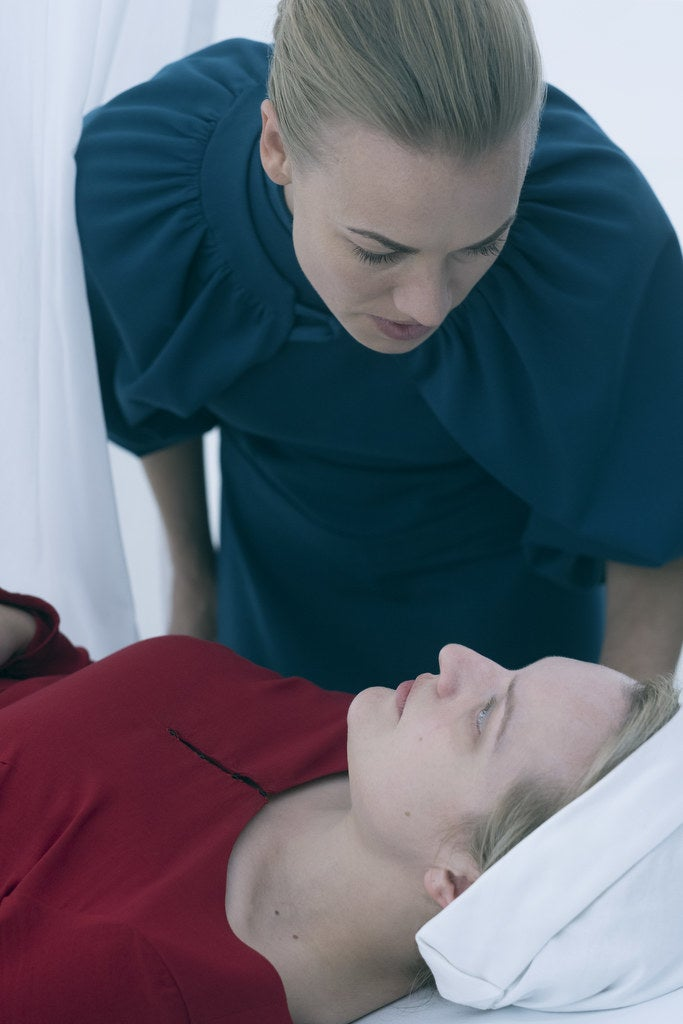 Yvonne Strahovski as Serena leans over Elisabeth Moss as June.