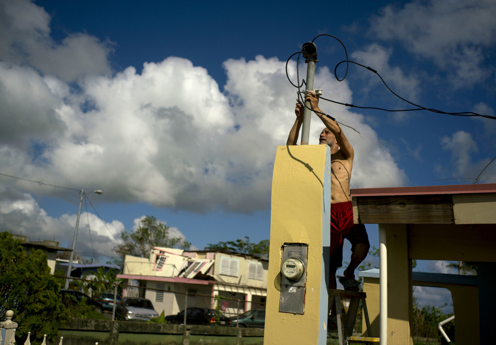 A resident tries to connect electrical lines downed by Hurricane Maria.