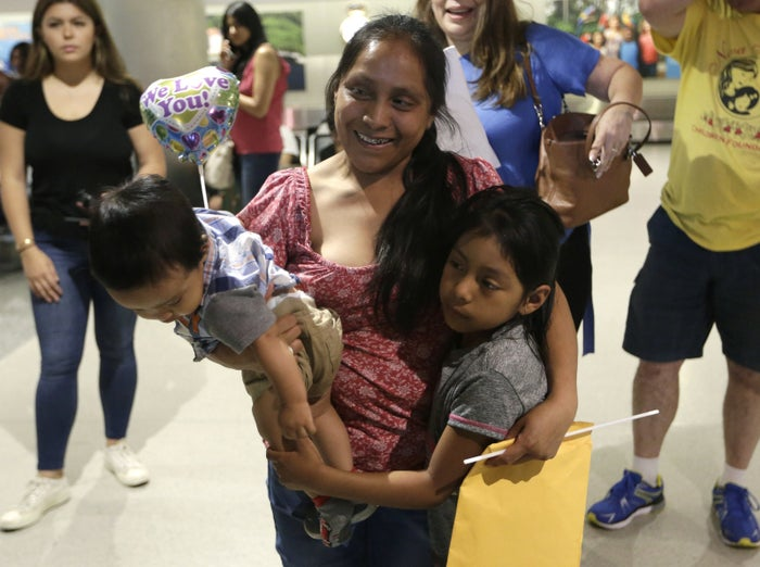 Buena Ventura Martin-Godinez, center, holds her son Pedro, left, as she is reunited with her daughter Janne (right) at Miami International Airport on July 1.