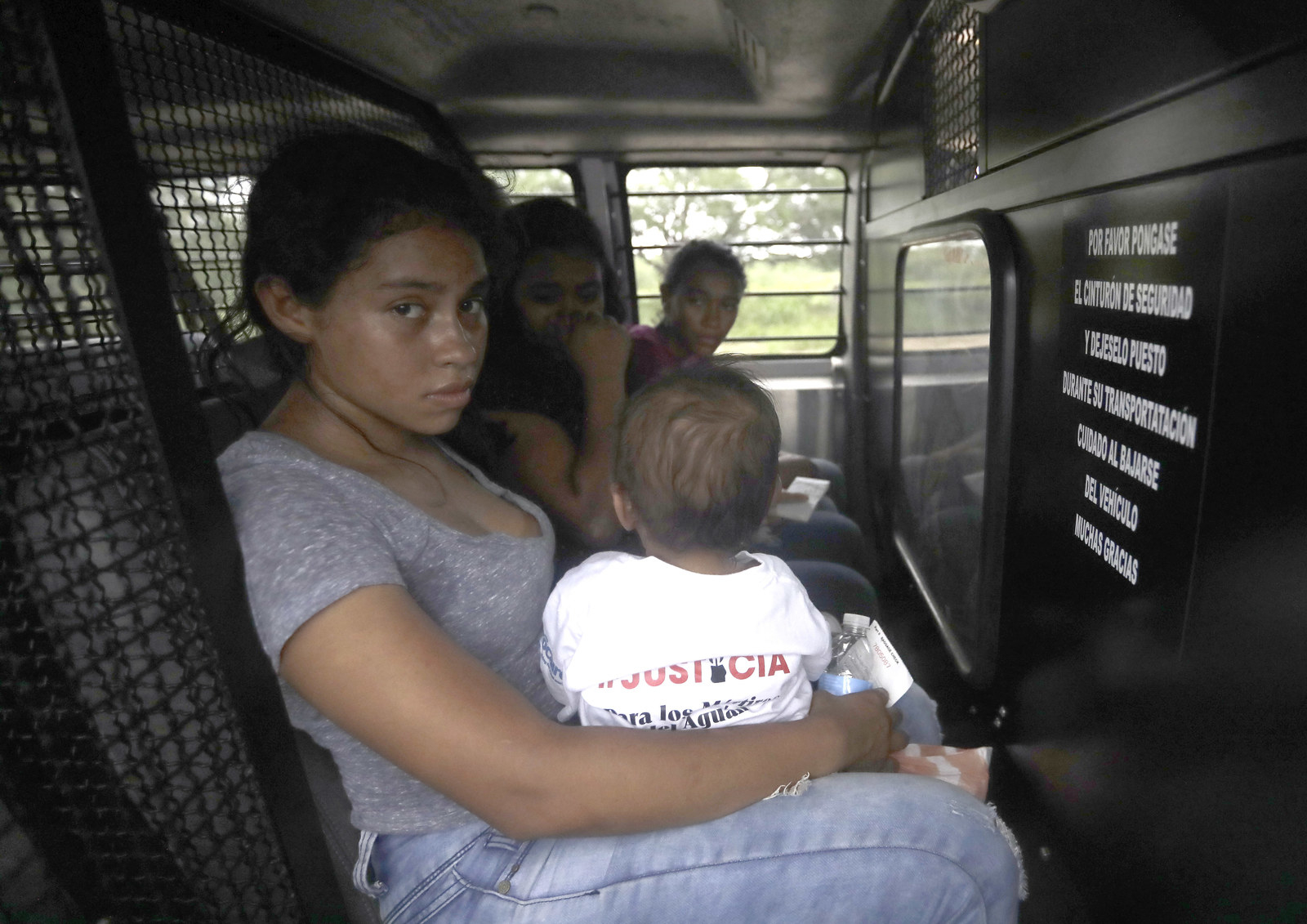 A mother migrating from Honduras holds her 1-year-old child in the back of a transport van after surrendering to Border Patrol agents on June 25, 2018.