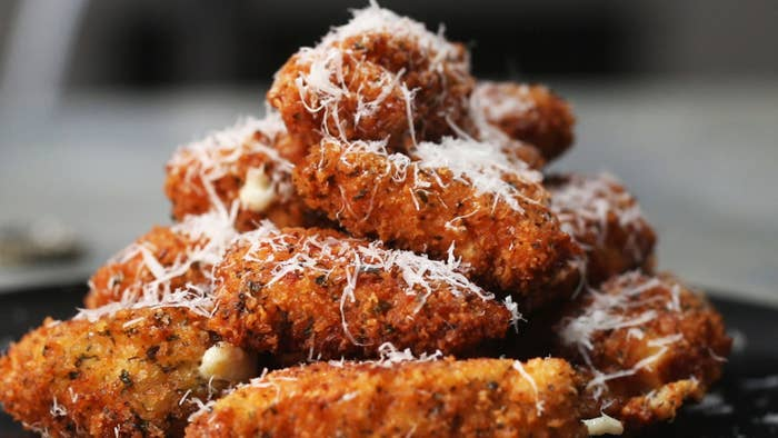 Chicken Parm BitesServings: 2-3Ingredients1 pound chicken tenders1 ball mozzarella cheese2 cups panko bread crumbs1 tablespoon garlic powder1 tablespoon dried basil1 tablespoon dried parsley1 tablespoon salt½ cup flour2 eggsOil to fry1 cup marinara saucePreparation1. Cut the chicken tenders into 1.5-inch pieces.2. Take a knife and carefully cut a hole into the chicken tenders. Make sure to not cut all the way to the other side.3. Stuff the holes with mozzarella cheese.4. Add garlic powder, dried basil, dried parsley, and salt to the panko bread crumbs.5. Batter the chicken in flour, egg, then panko bread crumb mixture.6. Add around 1-inch of oil to a pan and heat until around 350˚F/175˚C.7. Fry the chicken on both sides until fully cooked and golden brown.8. Serve with marinara sauce and garnish with more parmesan cheese. Enjoy!
