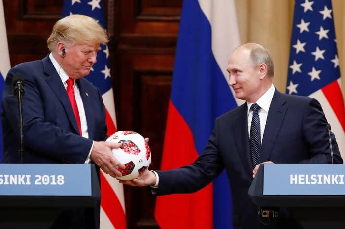 Putin handing Trump a soccer ball.