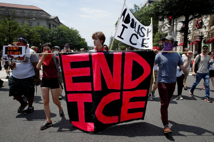 Immigration activists carry signs calling for the abolishment of ICE during a rally to protest the Trump administration's immigration policies.